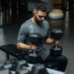 man-sitting-on-flat-bench-while-holding-two-dumbbells-3490348-4-1